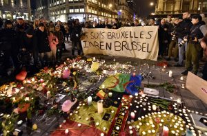 """Un grupo de personas sostene una pancarta en la que piede leerse """"Yo soy Bruselas"""", detrás de flores y velas que recuerdan a las víctimas de las explosiones de la capital belga, en la Plaza de la Bolsa, en el centro de Bruselas, el 22 de marzo de 2016. (Foto AP/Martin Meissner)"""