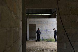 En esta imagen del 3 de julio de 2014 puede verse a policías estatales en el interior de una bodega en la que hay una cruz negra en una pared, cerca de las manchas de sangre dejadas en el suelo tras un tiroteo entre soldados mexicanos y supuestos criminales a las afueras de la localidad de San Pedro Limón en el Estado de México. La principal organización defensora de los derechos humanos de México anunció el miércoles 30 de marzo de 2016 que una corte militar absolvió a seis de los siete soldados acusados de indisciplina por los asesinatos de 2014. (Foto AP/Rebecca Blackwell, archivo)